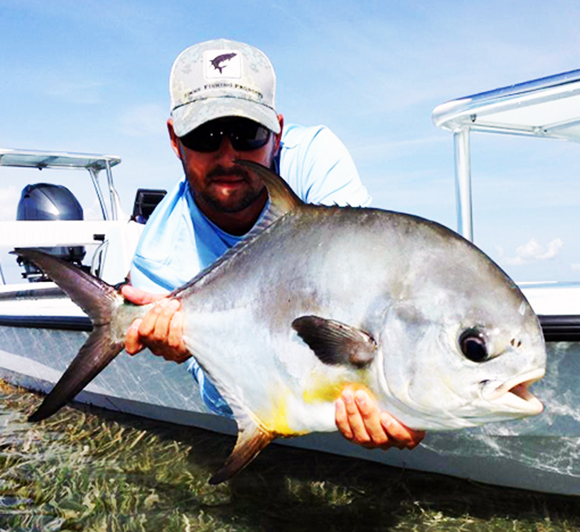 Key Largo Fishing Charters captain with Permit at boat side